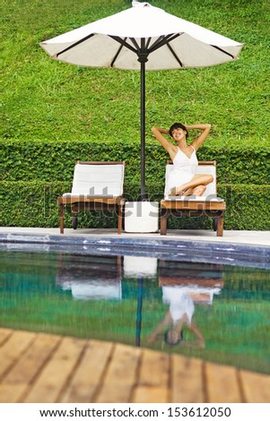 relaxed woman at poolside, bali