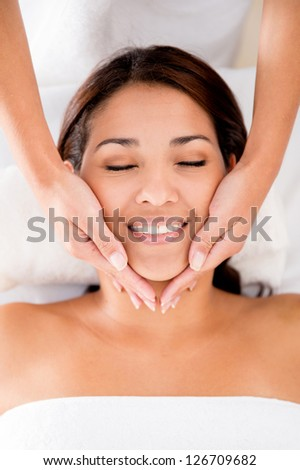 Relaxed woman at the spa getting a face massage