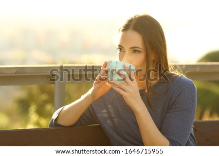 Relaxed woman drinking coffee sitting on a bench in a park at sunset