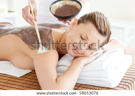 Relaxed woman enjoying a mud skin treatment in a Spa center