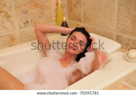 relaxed woman enjoying a warm bubble bath at home