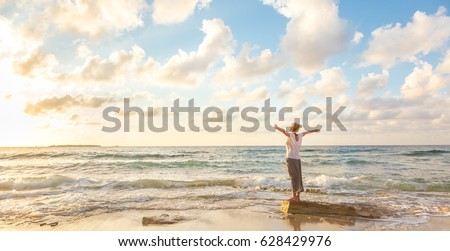 Relaxed woman enjoying sun, freedom and life an beautiful beach in sunset. Young lady feeling free, relaxed and happy. Concept of vacations, freedom, happiness, enjoyment and well being. #628429976