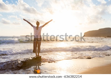 Relaxed woman enjoying sun, freedom and life an beautiful beach in sunset. Young lady feeling free, relaxed and happy. Concept of vacations, freedom, happiness, enjoyment and well being. #636382214