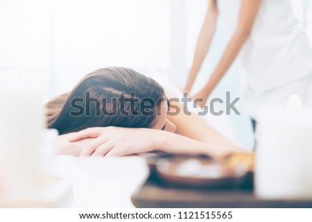 Relaxed woman getting back massage in luxury spa with professional massage therapist in white background. Wellness, healing and relaxation concept.