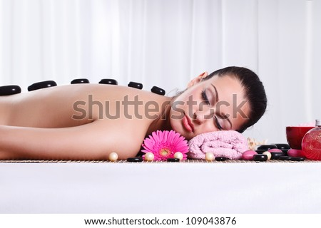 Relaxed woman in spa center with hot stone on back