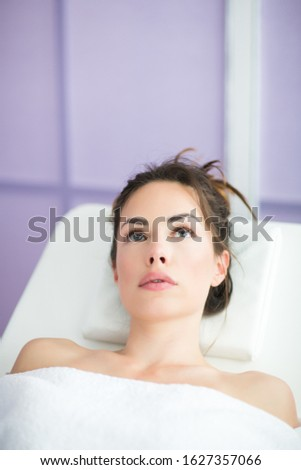 Relaxed woman is sitting in chair of beauty salon waiting for anti-aging treatments or an injection of hyaluronic acid