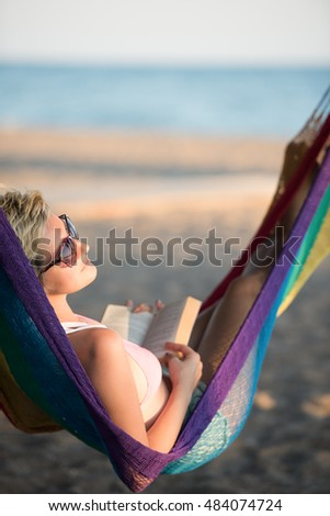 relaxed woman laying in hammock bed on beach and enjoy sunset while reading book #484074724