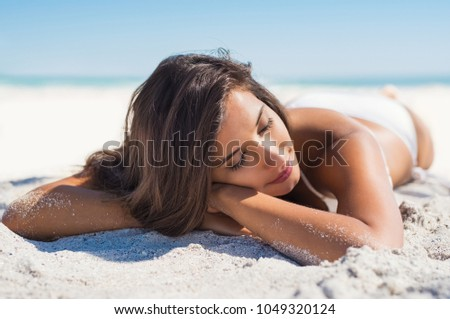 Relaxed woman lying down on sand during summer vacation. Beautiful girl lying down under the sun tanning in a tropical beach. Positive and serene young woman sunbathing at seaside with closed eyes.