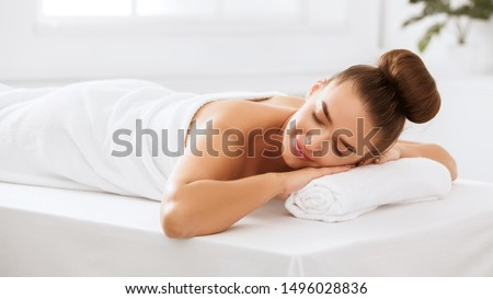 Relaxed woman lying in spa salon with closed eyes, waiting for massage
