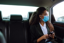 Relaxed woman passenger  in protective medical mask in the taxi car on a backseat with phone. Work on the way to the office. Covid-2019.