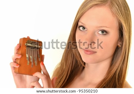 Relaxed woman playing on a version of the African instrument Kalimba