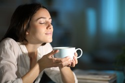 Relaxed woman smelling decaffeinated coffee in the night at home