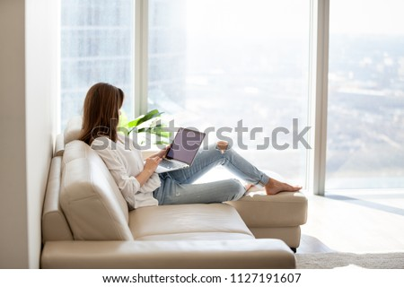 Relaxed woman using laptop in luxury home living room with big window, enjoying working, internet shopping, checking social network, reading news or communicating online with computer sitting on sofa