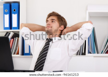 Relaxed young business man happy smile sitting at the desk, handsome businessman relaxing hold hand on head