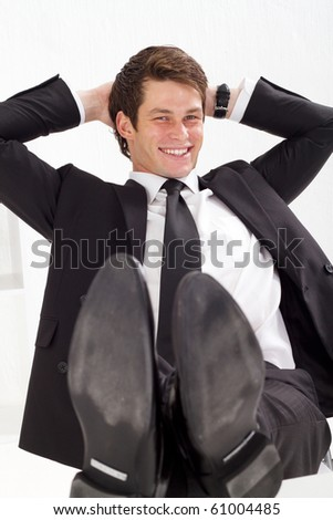 relaxed young businessman with arms behind his head