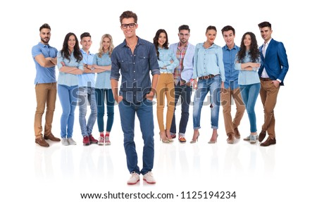 relaxed young casual leader standing in front of his team with hands in pockets and wearing glasses on white background #1125194234