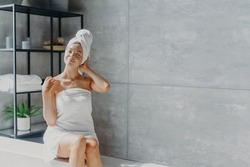 Relaxed young Caucasian female model wears towel wrapped on head, feels refreshed after taking shower, has healthy clean soft skin, poses in cozy bathroom. Women, beauty and hygiene concept.