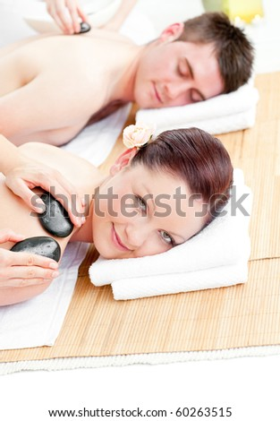 Relaxed young couple receiving a back massage with hot stones in a spa center