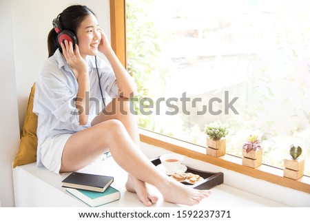 Relaxed young girl lying on cozy couch at home enjoying reading a book. Rest and relax concept.