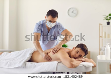Relaxed young male client lying on massage table in spa center and enjoying body massage done by professional masseur or physiotherapist wearing medical face mask to protect from virus at work Stockfoto ©
