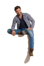 Relaxed young man in boots, jeans and unbuttoned lumberjack shirt is sitting on a top, smiling and looking at camera. Full length studio shot isolated on white.
