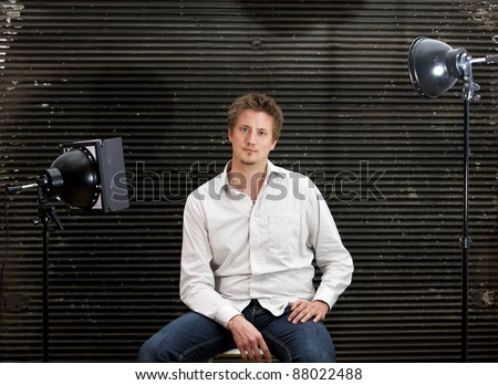 Relaxed young man posing in front of the camera in a photo studio with a serious look.  His face is marked by smartness, determination and self-confidence.