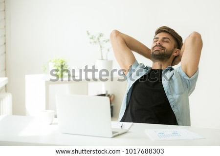 Relaxed young man resting from work on laptop holding hands behind head, successful entrepreneur relaxing feels happy breathing fresh air, smiling man enjoy break stretching in home office workplace