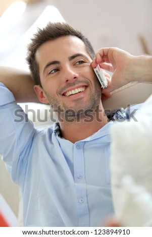 Relaxed young man talking on the phone in sofa