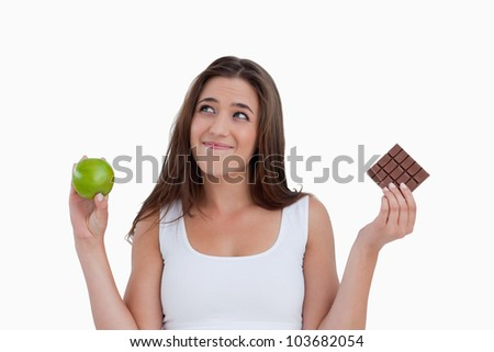 Relaxed young woman holding an apple and chocolate against a white background