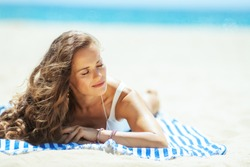 relaxed young woman in white swimwear laying on a striped towel on the seashore. stressed free beach retreat. Sun protected hair. Sunny summer midday. getting vitamin D after long winter months.
