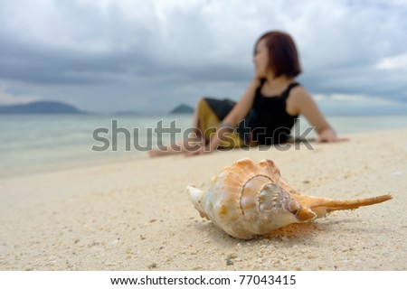 Relaxed young woman sits as background while the crab shell in focus as foreground