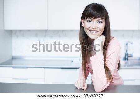 Relaxed young woman standing at the kitchen counter. Portrait of beautiful relaxed young woman standing at the kitchen counter - Indoor