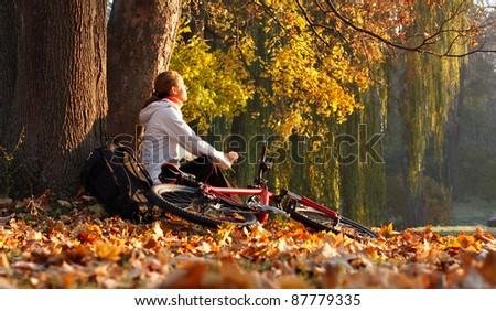 Relaxes woman cyclist with bike sits among fallen leaves autumn morning in nature illuminated by the bright rays of the rising sun and enjoy recreation