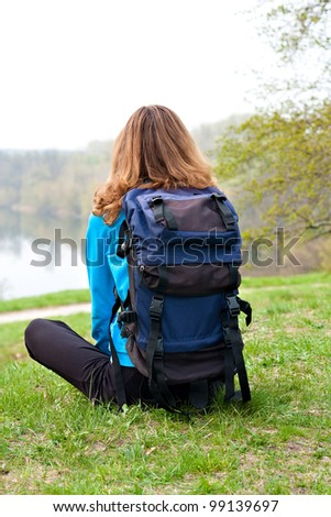 Relaxes woman tourist sitting on the grass. Back to us. Beautiful front view