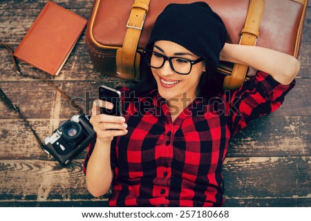 Relaxing after long trip. Top view of beautiful young woman in headwear lying on the floor holding mobile phone and smiling #257180668