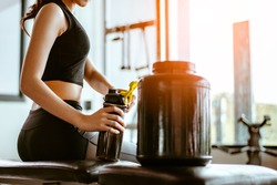 Relaxing after training.beautiful young woman looking away while sitting  at gym.young female at gym taking a break from workout.woman brewing protein shake.