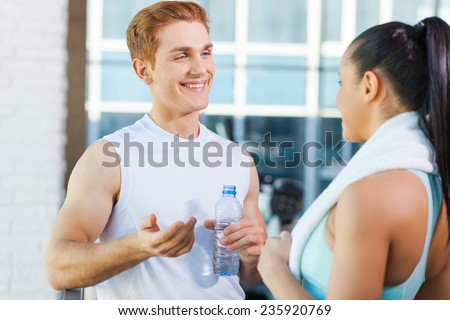 Relaxing after work out. Beautiful young sporty couple talking and smiling while standing in gym