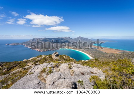 Relaxing amazing mountain viewpoint stunning view to Wineglass Bay sandy beach blue water and enjoyng warm sunny blue sky after hiking on top, Freycinet National Park, Mount Amos, Tasmania, Australia #1064708303