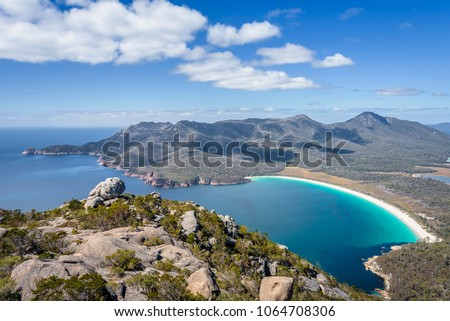 Relaxing amazing mountain viewpoint stunning view to Wineglass Bay sandy beach blue water and enjoyng warm sunny blue sky after hiking on top, Freycinet National Park, Mount Amos, Tasmania, Australia #1064708306