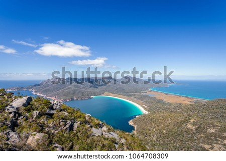 Relaxing amazing mountain viewpoint stunning view to Wineglass Bay sandy beach blue water and enjoyng warm sunny blue sky after hiking on top, Freycinet National Park, Mount Amos, Tasmania, Australia #1064708309