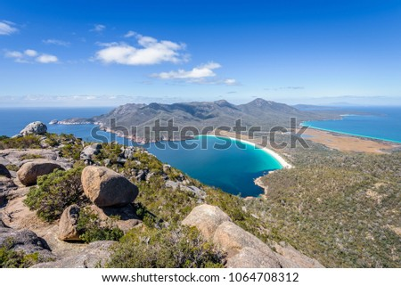 Relaxing amazing mountain viewpoint stunning view to Wineglass Bay sandy beach blue water and enjoyng warm sunny blue sky after hiking on top, Freycinet National Park, Mount Amos, Tasmania, Australia #1064708312