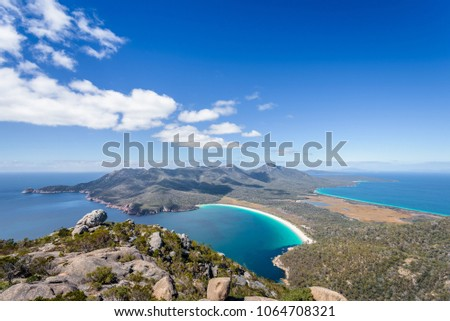 Relaxing amazing mountain viewpoint stunning view to Wineglass Bay sandy beach blue water and enjoyng warm sunny blue sky after hiking on top, Freycinet National Park, Mount Amos, Tasmania, Australia #1064708321