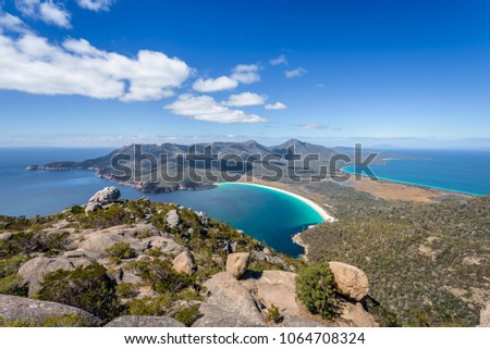 Relaxing amazing mountain viewpoint stunning view to Wineglass Bay sandy beach blue water and enjoyng warm sunny blue sky after hiking on top, Freycinet National Park, Mount Amos, Tasmania, Australia #1064708324