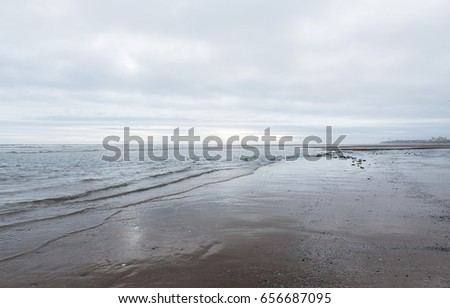 relaxing and gentle calming waves flowing into a beach on an gloomy overcast day