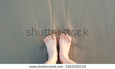 relaxing and stretch barefoot of woman on sand of beach #1063320518