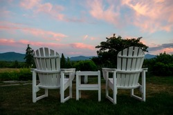 Relaxing Anirondack Chairs looking out on a beautiful mountain sunset