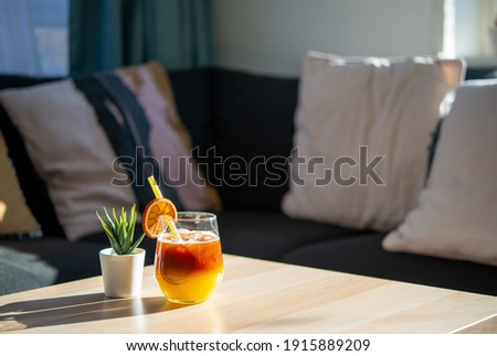 Relaxing at home after work drink concept.  Exotic cocktail made from Black Coffee Rum mixed with sweet orange juice on Iced. Iced Coffee background in the living room with free copy space for text.