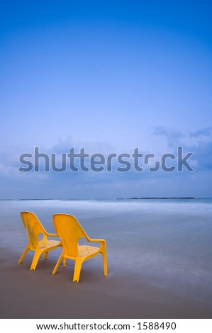 Relaxing at the beach, two yellow chairs, calm blue sea and gentle clouds