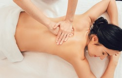 Relaxing back massage, massage therapist massages the back of a beautiful woman, relieve muscle tension back, top view