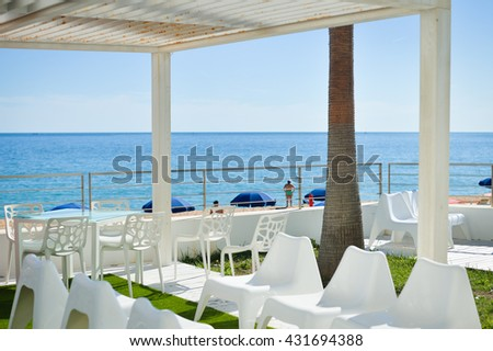 Relaxing background ocean beach view with table chairs, sunshine blue sky #431694388